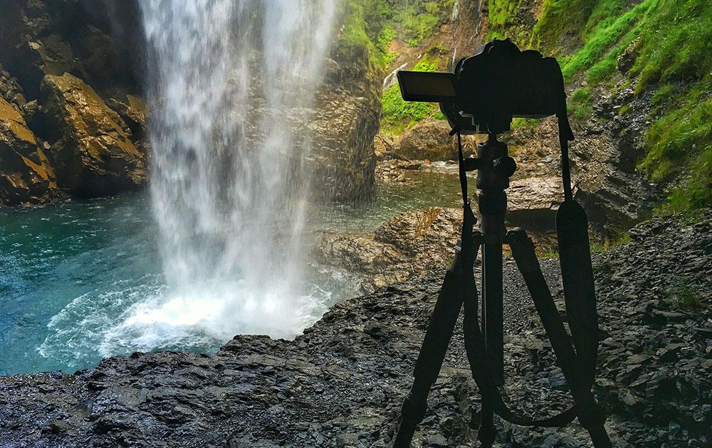 Camera on tripod filming a waterfall